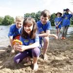 Mädchen mit Lupe am Wasser, im Hintergrund sind 4 andere Kinder zu sehen.